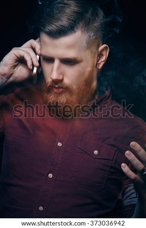Bearded freaky guy smoking cigar and talking on the phone.