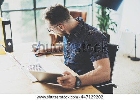 Bearded graphic designer working wood table laptop Modern Interior Design Loft Place.Man Work Coworking Studio.Use contemporary Notebook,typing keyboard.Blurred Background.Creative Business Startup - stock photo
