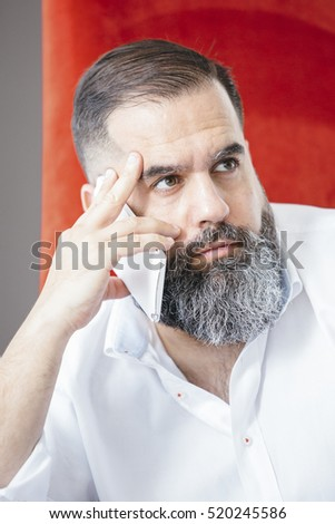 Bearded handsome man looking away while phoning