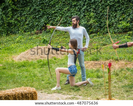 Bearded handsome man shows the girl where to shoot from the bow