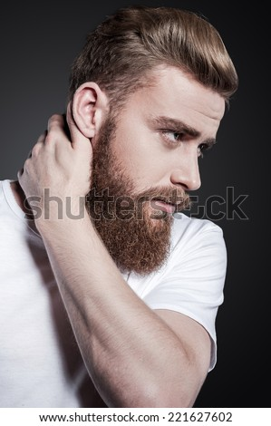 Bearded handsome. Portrait of thoughtful young bearded man touching his neck and looking away while standing against grey background - stock photo