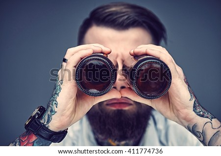 Bearded hipster man holding beer bottles like binocular.