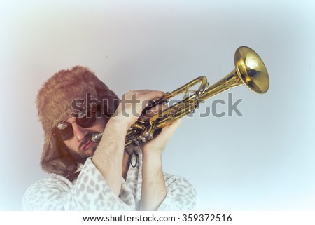 Bearded hipster plays jazz trumpet in leopard print bathrobe