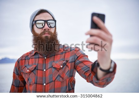 bearded hipster taking selfies with smartphone on the salt flats - stock photo