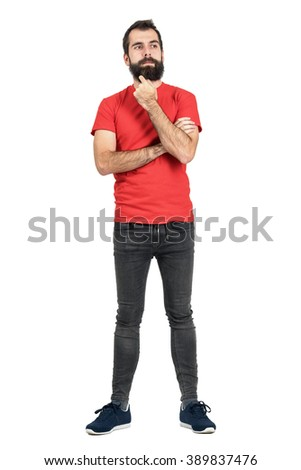 Bearded hipster thinking and touching his beard looking away. Full body length portrait isolated over white studio background. - stock photo