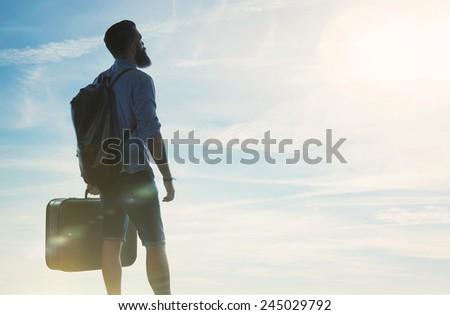 Bearded hipster traveler looking at sun - stock photo