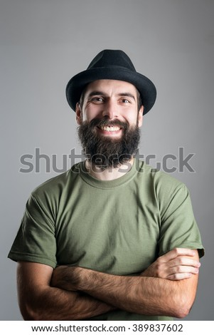 Bearded hipster wearing hat with upper lips piercing friendly laughing at camera.  Headshot portrait over gray studio background with vignette.  - stock photo
