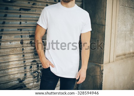 Bearded hipster wearing white blank t-shirt and blue jeans, standing on the street - stock photo