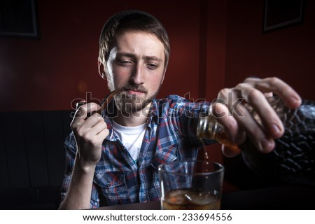 Bearded hipster with tobacco pipe and cognac.