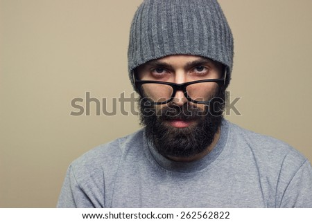 Bearded hipster young man with glasses and hat looking at camera, closeup