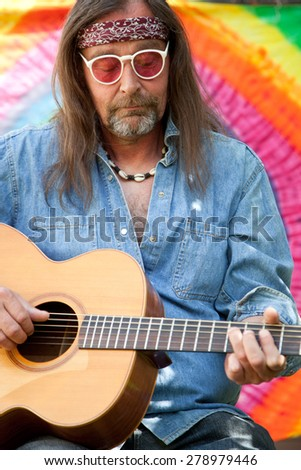 Bearded long-haired middle-aged hippie man wearing red plastic sunglasses, headband, blue denim shirt and handmade necklace while playing the guitar, portrait on spectral background