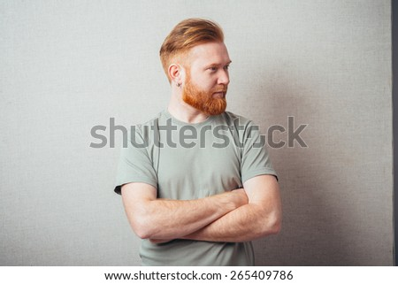 bearded man folded his hands and looking to the side - stock photo