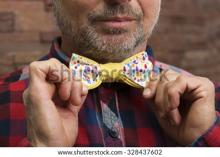 Bearded man holding a colorful bow tie