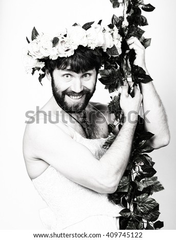 bearded man in a woman's wedding dress on her naked body, clinging to the vine. on his head a wreath of flowers. funny bearded bride, black and white