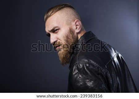 bearded man in leather jacket looking pensively into the distance - stock photo