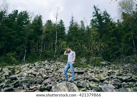 Bearded man in mountain forest. Hiker - stock photo