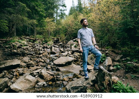 Bearded man in mountain forest. Hiker crosses a river at the ford - stock photo