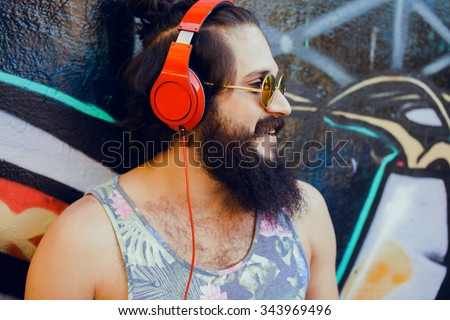 Bearded man,lifestyle portrait of hipster man,cool beard.Mans hairstyle.haircut,hairdresser.Stylish man posing with cool hairstyle,wall,ready to car trip.Happy active,NYC street,California,east coast. - stock photo