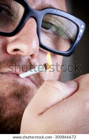 Bearded man lights a cigarette. Bespectacled man with a cigarette in his mouth and lit lighter. Portrait of a bearded with eyeglasses igniting a cigarette. - stock photo