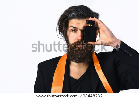 Bearded man, long beard. Brutal caucasian hipster with moustache have acid orange tie on suit and holding perfume isolated on white studio background