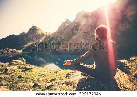 Bearded Man meditating yoga relaxing alone sitting lotus pose on stone Travel healthy Lifestyle concept lake and mountains sunny landscape on background outdoor  - stock photo