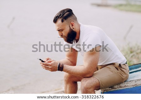 bearded man on the boat with phone