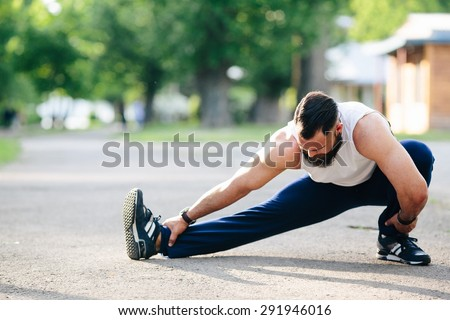 bearded man perform various exercises and stretches - stock photo