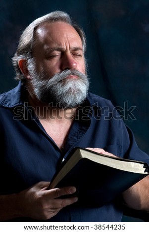 Bearded man praying while holding Holy Bible. - stock photo