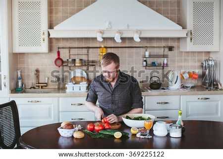 bearded man preparing vegetable salad in the kitchen - stock photo