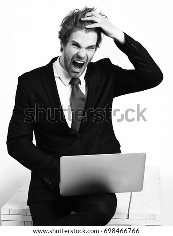 Bearded man, short beard. Caucasian stylish shouting business man with moustache in elegant black suit and red tie holding laptop in studio on white background