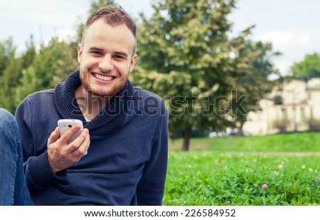 Bearded man sitting in park on blanket. He is using mobile phone. Outdoor photo. He looks relaxed. - stock photo