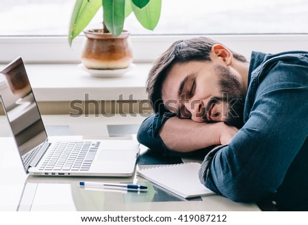 Bearded man sleeping at his working place home office with head on the desk - stock photo