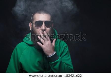 Bearded man, wearing a green sweatshirt and sunglasses, smoking - stock photo