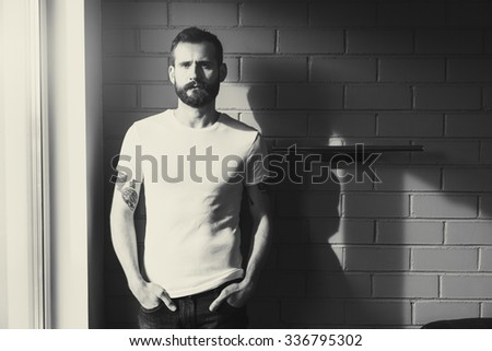 bearded man wearing blank white t-shirt on brick wall background. black and white toning
