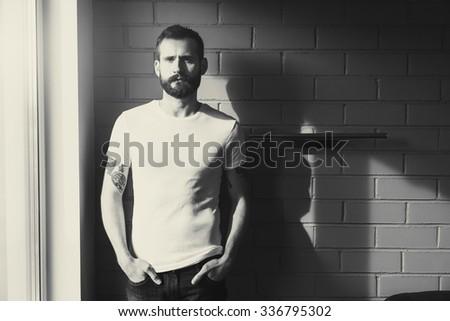 bearded man wearing blank white t-shirt on brick wall background. black and white toning - stock photo