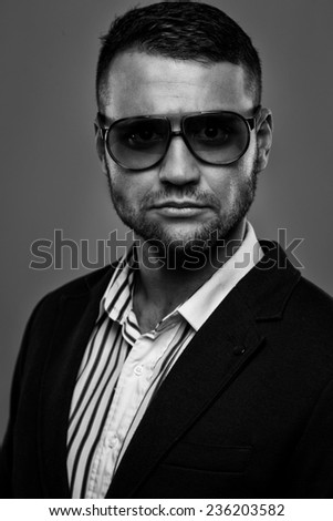 Bearded man wearing sunglasses in a suit - stock photo