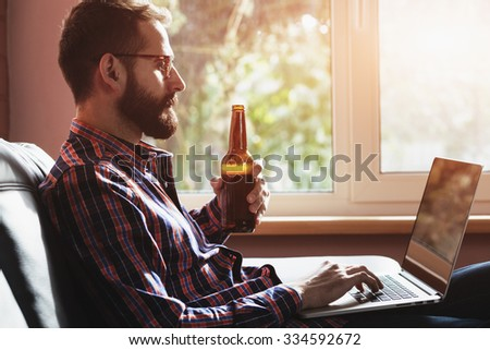 bearded man with laptop drinking bottle of beer - stock photo