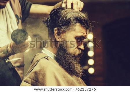 Bearded man with long beard, brutal, caucasian hipster with moustache, with stylish hair, haircut, getting powder on skin with makeup brush by barber or hairdresser hands at barbershop