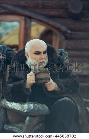 bearded man with long beard on serious face holding wood cup with iron decoration in fur coat outdoor sitting on wooden chair
