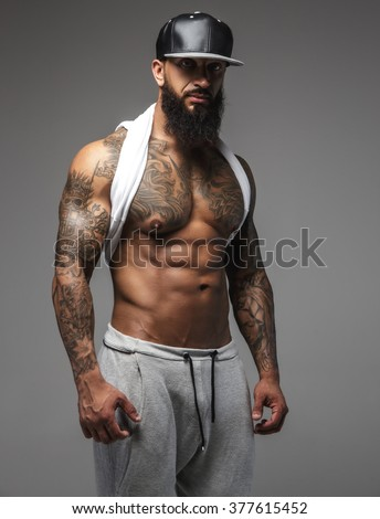 Bearded man with muscular tattooed body standing on a grey background. - stock photo