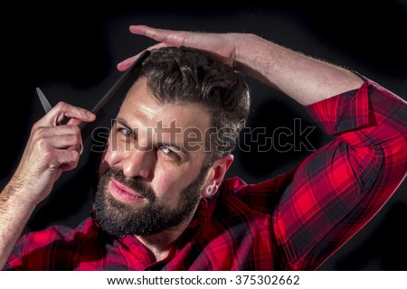 Bearded man with red plaid shirt combs his hair, on black