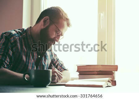 Bearded man writing with pen and reading books at table - stock photo