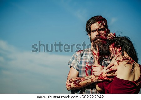 Bearded man zombie bloody hipster and creepy girl young woman with wounds and red blood outdoors on blue sky