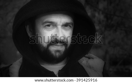 Bearded mature man in the demi-season jacket with a hood. Street photography