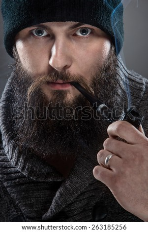 Bearded mezczyna dressed like a sailor. He wears a black cap and a pipe in his mouth. - stock photo