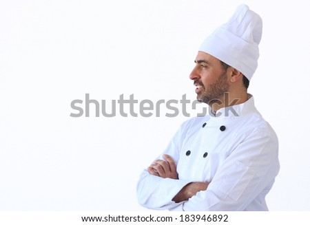 Bearded middle-aged chef in white toque and uniform standing looking at the copy space - stock photo