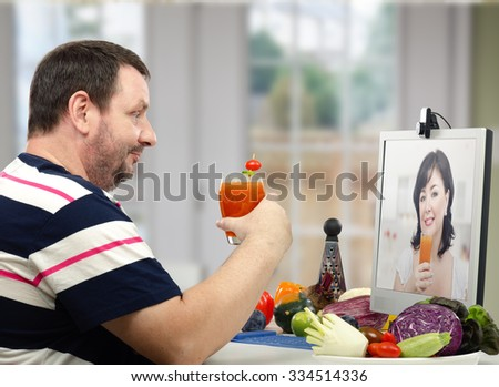 Bearded middle aged man in striped t-shirt has just learned how to make a detox drinks to lose weight at home during on-line lesson with nutritionist - stock photo