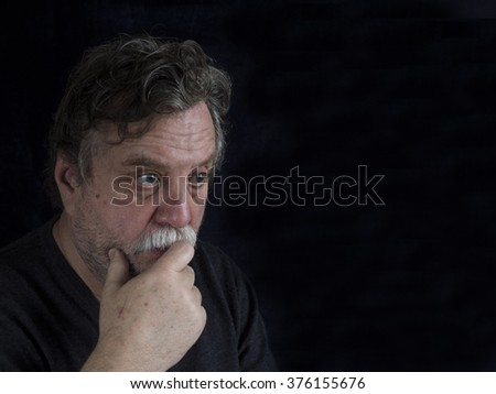 bearded middle-aged man on dark background