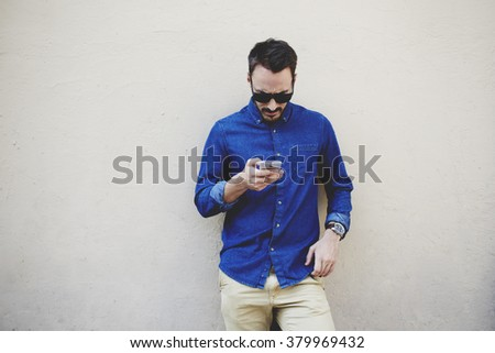 Bearded modern businessman concentrated reading world news in internet via mobile phone during work break, hipster guy watching video on cell telephone while standing against wall with copy space area - stock photo