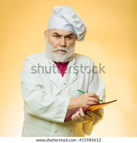Bearded senior cook man pointing recipe at the cookbook at the kitchen in hat on yellow background